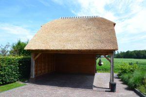 Houten schuur met rieten dak en carport